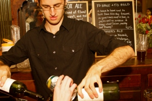 """Bartender Eric pouring """"sangria."""" The home-brew beer menu can be seen in the background."""